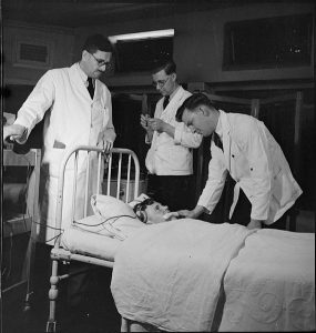 Photo: male nurses assist an English doctor, 1943