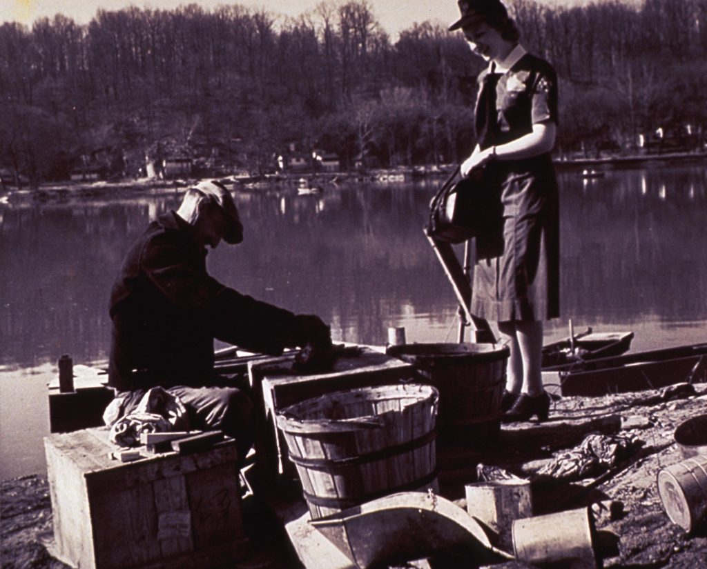 Public health nurse standing while visiting patient sitting on river shore sorting fish in barrels.